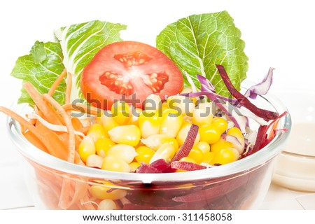 Fresh mixed vegetables salad in glass bowl.