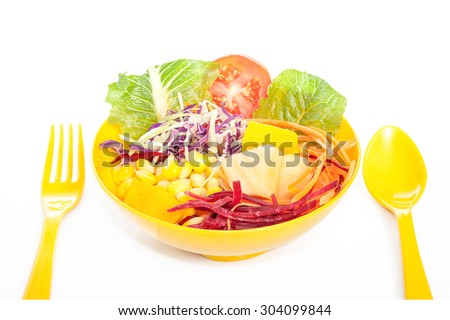 Fresh mixed vegetables salad in yellow bowl.