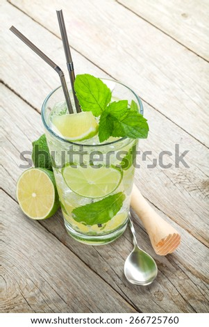 Fresh mojito cocktail and bar utensils. On wooden table - stock photo