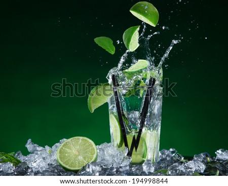 Fresh mojito cocktail in freeze motion splashing, close-up. - stock photo