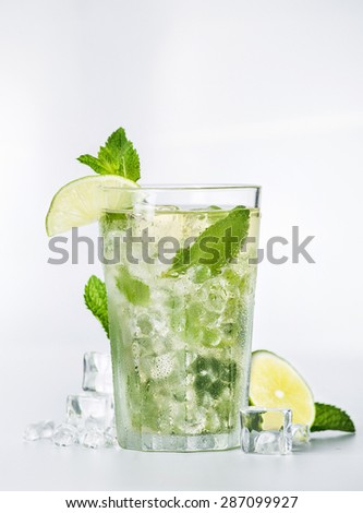 Fresh mojito cocktail with mint, lime and ice cubes on white background
