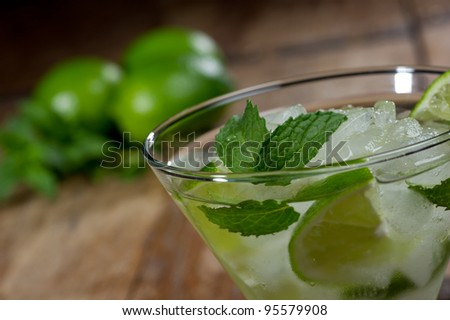 Fresh mojito in a lowball glass on a rustic table garnished with limes and mint leaves.