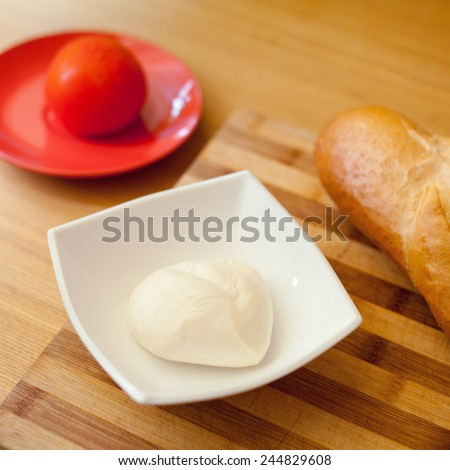 Fresh mozzarella and tomato on red and white plate. Wooden desk and basil leaves on a background. Preparation to caprese salad. Food, restaurant, menu, italian meal. Nobody, macro perspective. - stock photo