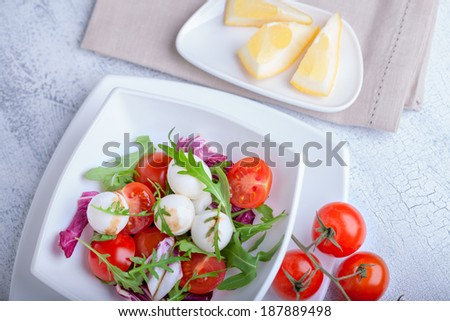 Fresh mozzarella balls served with spicy rocket leaves and cherry tomatoes. - stock photo