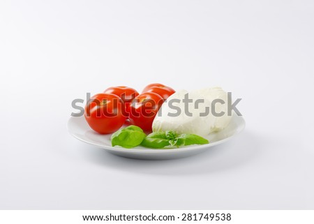 fresh mozzarella, basil and tomatoes - ingredients for caprese salad on white plate - stock photo