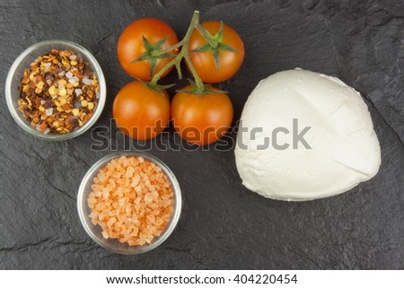 Fresh mozzarella cheese on slate board. Healthy diet meals. Preparing food for guests. Traditional meal. Mozzarella and tomatoes. Dark grey background.  - stock photo