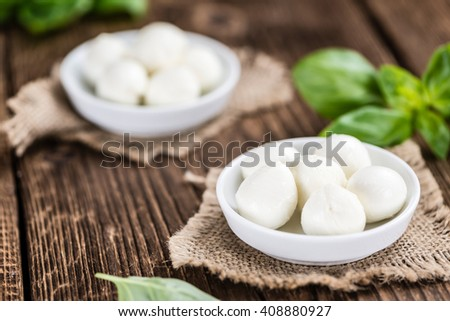 Fresh Mozzarella (close-up shot) on wooden background (selective focus)