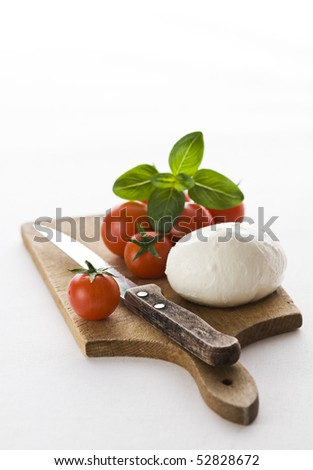 Fresh mozzarella, tomato and basil on wooden board - stock photo