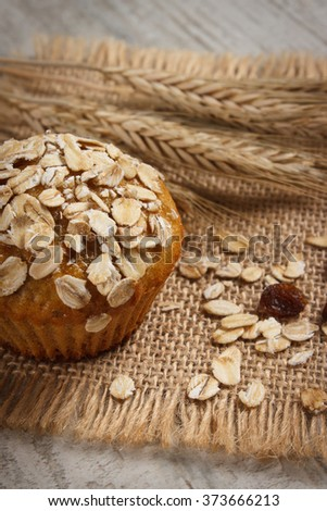Fresh muffin with oatmeal baked with wholemeal flour and ears of rye grain, concept of delicious, healthy dessert or snack