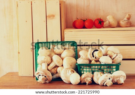 fresh mufresh mushroom champignon in green rustic basket on wooden table - stock photo