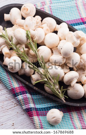 Fresh mushrooms in  bowl on colorful towel. Selective focus. Rustic style. - stock photo
