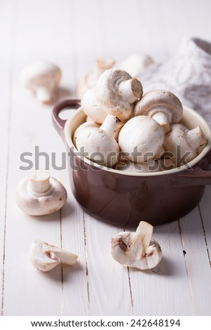 Fresh mushrooms in bowl on white wooden background. Selective focus.  - stock photo