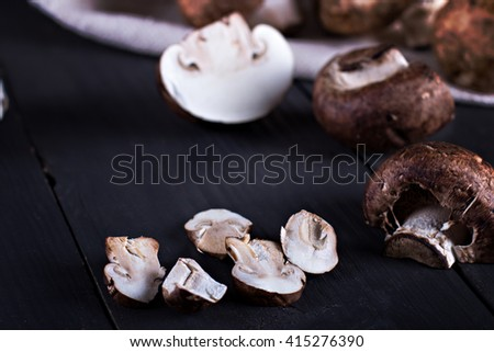 Fresh mushrooms  on a black board. Champignon mushrooms - stock photo