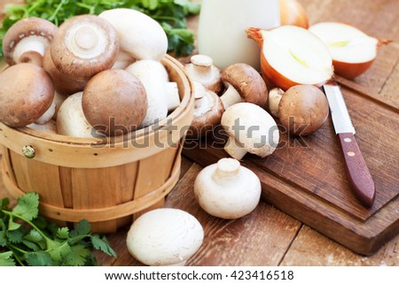 Fresh mushrooms, onions, parsley, sour cream on wooden background - mushroom cream soup preparation