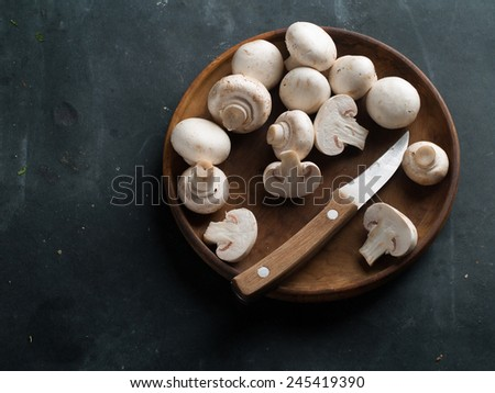 Fresh mushrooms with knife on wooden plate, selective focus - stock photo