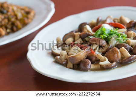 Fresh mushrooms with oyster sauce in white plate. - stock photo