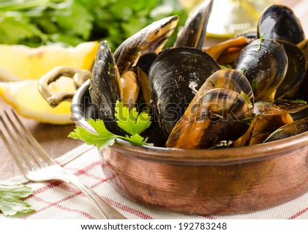 Fresh mussel with herbs, lemon and wine on white background - stock photo