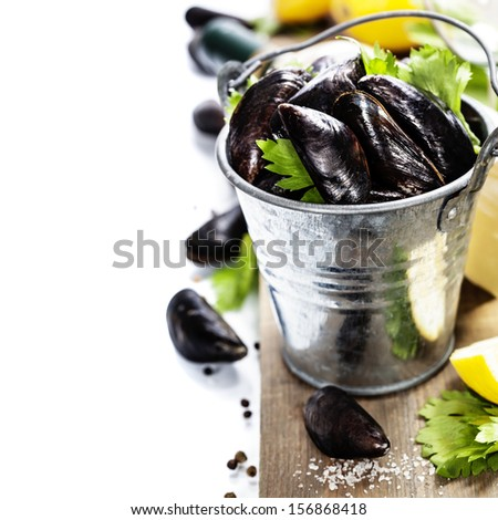 Fresh  mussels ready for cooking on wooden background - stock photo