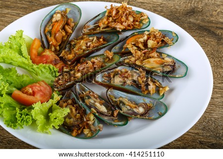 Fresh Mussels with fried garlic served tomato, salad and cucumber - stock photo