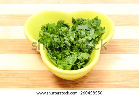 Fresh, natural and green chopped parsley in yellow dish lying on wooden cutting board, concept for healthy eating - stock photo