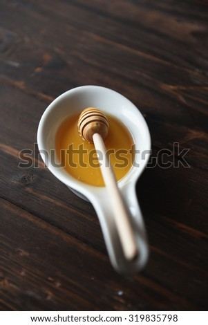 Fresh natural honey in a bowl with honey spoon on a wooden vintage table - stock photo