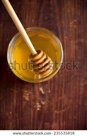 Fresh natural honey in a jar with honey spoon on a wooden rustic vintage table - stock photo