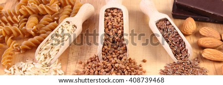 Fresh, natural ingredients and products containing magnesium and dietary fiber, healthy food and nutrition, wholemeal pasta, buckwheat, brown rice, linseed, almonds, chocolate - stock photo