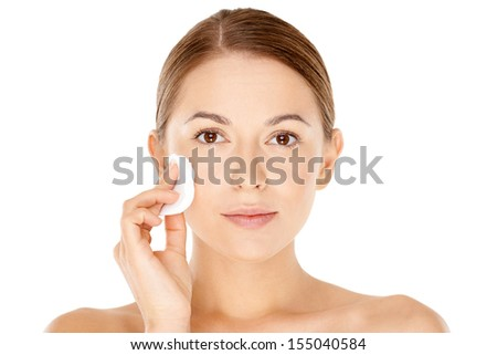 Fresh natural portrait of a beautiful young woman cleaning her face with a cotton pad wiping her cheek  isolated on white - stock photo