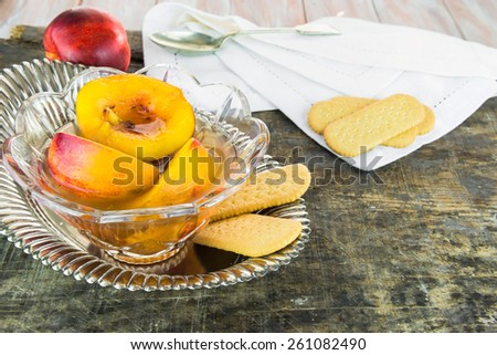 Fresh nectarines in sweet honey, vanilla and whiskey sauce with shortbread on wooden background - stock photo
