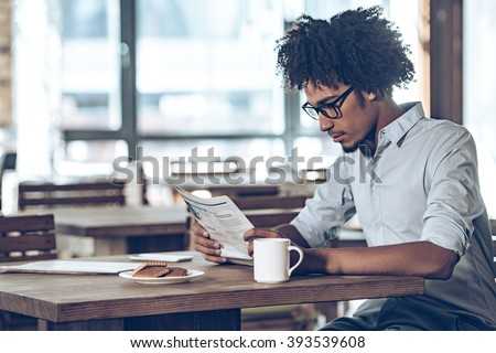 Fresh newspaper in the morning. Side view of young African man in glasses reading newspaper while sitting in cafe - stock photo
