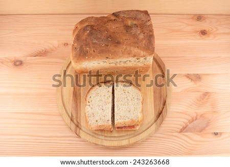 Fresh oat and linseed bread with two peanut butter and jelly sandwiches on a wooden board - stock photo