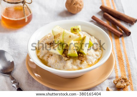 Fresh oatmeal porridge with apples, honey and cinnamon close up