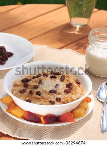 Fresh oatmeal topped with raisons, melted butter, and brown sugar. - stock photo