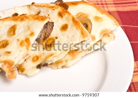 fresh off the stove a steak Quesadilla on a white plate