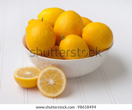 Fresh off the Tree, Sweet and Sour Meyer Lemons in a Bowl on White Bead Board Surface with One Lemon cut in half. - stock photo