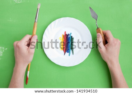 Fresh oil paint and painting instruments served like a dish - stock photo