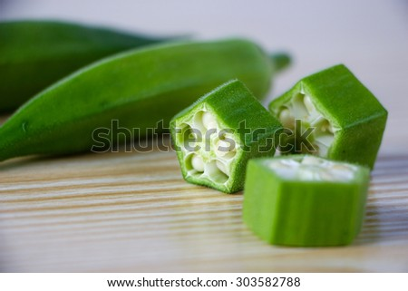 Fresh okra on the wooden table background. - stock photo
