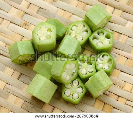 fresh okra sliced on plate isolated on white - stock photo