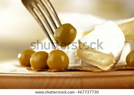 fresh olives and cheese on a wooden table on a sunny morning