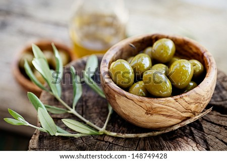 Fresh olives and olive oil  on rustic wooden background. Olives in olive wood. - stock photo