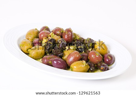Fresh olives and prunes sauce in a white bowl.