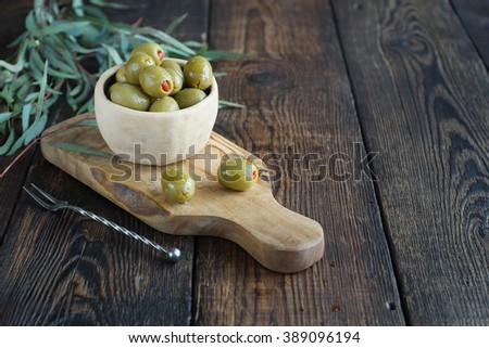 Fresh olives in ceramic bowl and vintage fork on board on a dark rustic wooden background. Olives on olive wood. - stock photo