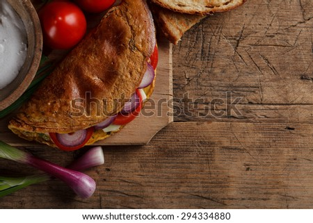 Fresh omelette with onions and tomatoes on wooden cutting board - stock photo