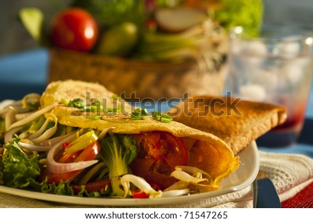 Fresh omelette with vegetables on a plate and vegetables in the background - stock photo