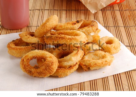 Fresh onion rings on a sheet of white paper - stock photo