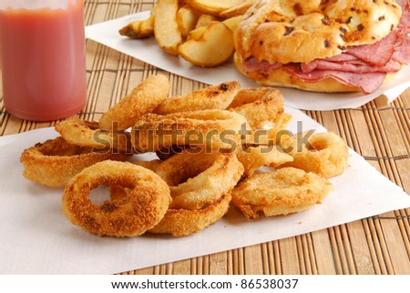Fresh onion rings with a roast beef sandwich in the background - stock photo