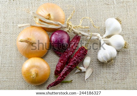 Fresh onions, garlic and dried peppers on a vintage tablecloth
