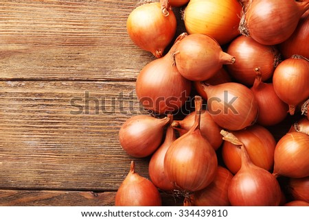 Fresh onions on wooden background - stock photo