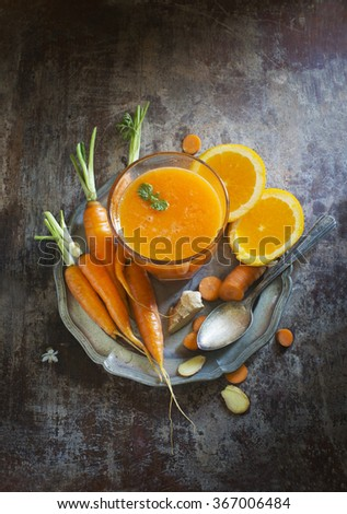 Fresh orange and carrot juice on moody rustic wooden background. - stock photo