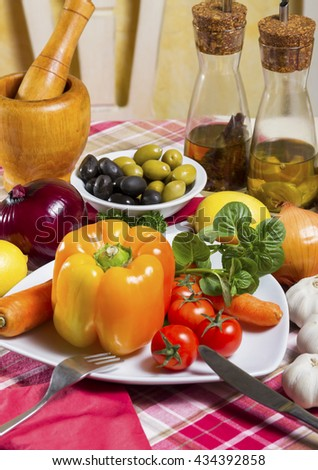 Fresh, orange bell pepper, basil, cherry tomatoes and carrot next to the white bowl with olives, onion, garlic, two glass bottles with spicy edible oil - vegetable, herb, curative, vegan food. - stock photo